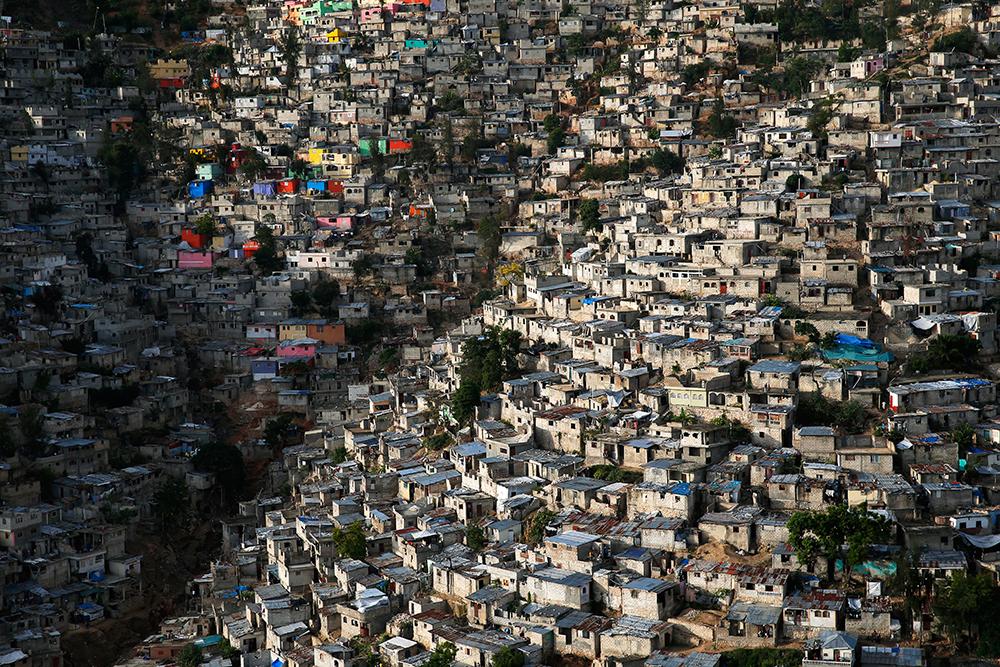 Jalousie, bidonville bordant la ville de Pétionville, banlieue de Port-aux-Prince, Haïti (18° 30' 41.57'' N – 72° 17' 38.80'' O). © HUMAN The Movie Une partie du quartier de Jalousie a été repeinte de couleurs vives en 2012. Mais les maisons restent, pour la plupart, dépourvues d'eau et d'électricité. Après le séisme de 2010, 1,3 million de personnes se sont retrouvées sans abri. Beaucoup d'entre elles ont été relogées dans des camps, mais la reconstruction tarde. À l'échelle de la planète, les bidonvilles hébergent plus de 826 millions de personnes ; ils accueillent environ 27 millions de personnes supplémentaires chaque année.