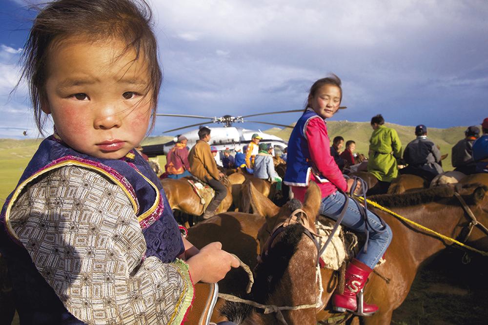 Un hélicoptère EC145, en Mongolie, au milieu de jeunes semi-nomades préparant une course à cheval.